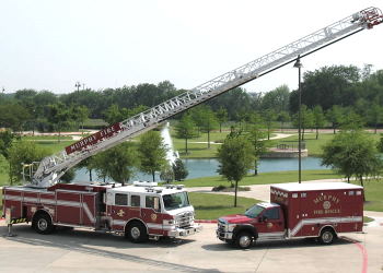Department fire trucks in front of an area lake